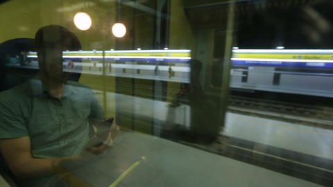 Train slowly stopping at empty station platform, guy with gadget by window Live Action