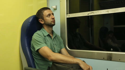 Exhausted male traveler sitting in his seat going to another city by night train Footage
