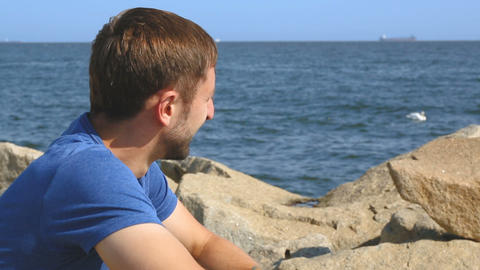 Happy young male sitting on stones at embankment and enjoying beautiful seascape Footage