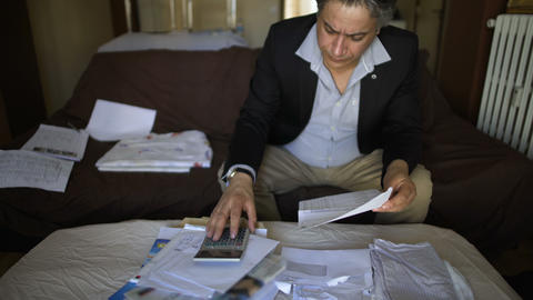 Male houseowner checking mail and bills, thoroughly counting cost of utilities Footage