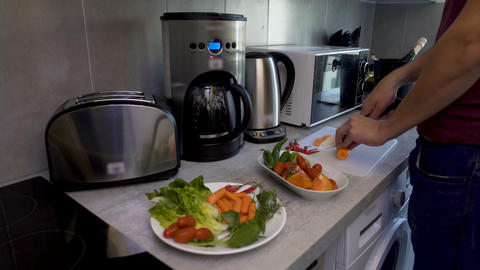 Cheerful biracial guy preparing salad at his kitchen waiting for relatives visit Footage
