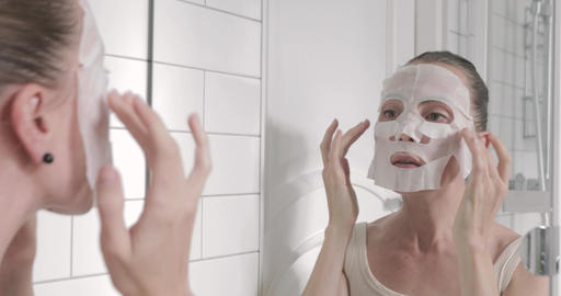 woman applying mask on her face looking in mirror Footage