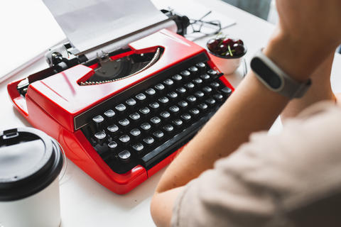 Woman writer thoughtfully working on a book on her Desk red typewriter フォト