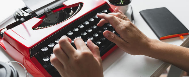 Woman hand working with bright red vintage typewriter Fotografía