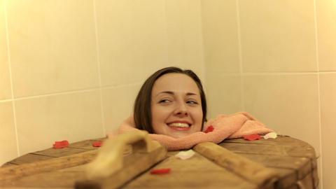 Young woman is in cedar barrel in spa salon indoors.... Stock Video Footage