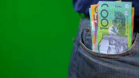 Man putting Australian cash into jeans pocket against green screen, macro close ビデオ