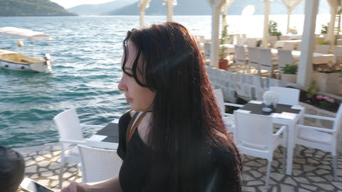 Young woman with a phone on the waterfront GIF