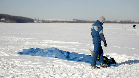 Winter fun. People on the frozen lake are engaged in paragliding and winter GIF