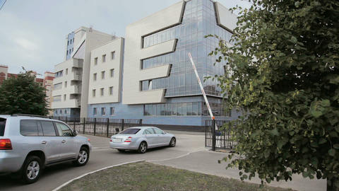 cars pass checkpoint and drive to modern building Archivo