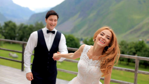 Wedding day. Happy newlyweds have fun against the backdrop of the mountains Footage