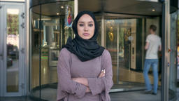 Young serious muslim girl is standing with arms crossed in daytime, watching at Footage