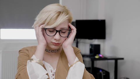 Young blonde businesswoman suffering from migraine rubbing her head exhausted Live Action