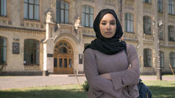 Young serious muslim girl is standing with arms crossed in daytime in summer Footage