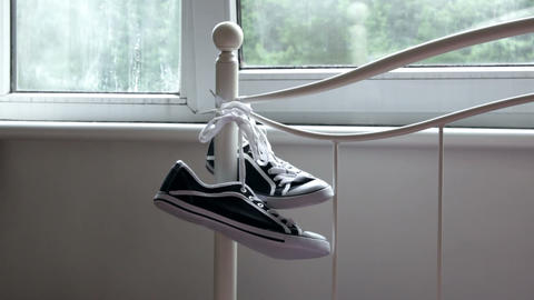 Pair of sneakers hanging on the bed rail Footage