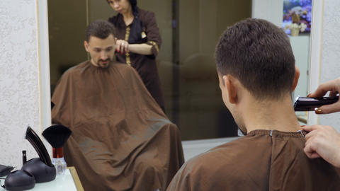 Hairdresser cuts hair of man with electric razor Footage