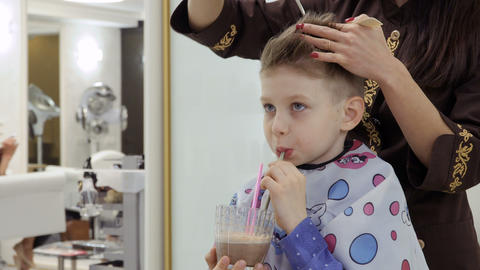 Cute boy drinks cocktail during hairdresser cuts his hair in barbershop Footage