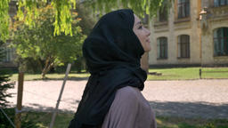 Young sweet muslim girl in hijab is smiling and going to university in daytime Footage