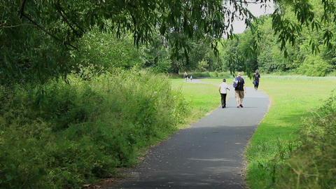Path in the park - teenage boy and father walking along from school Footage