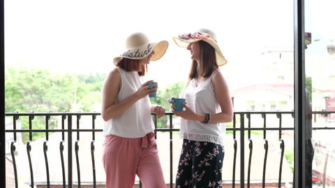 Two gorgeous young women in large summer hats on the balcony drinking coffee and Footage