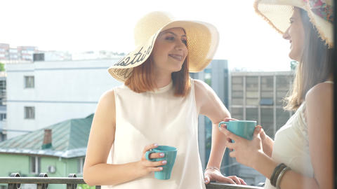 Two gorgeous female friends wearing large summer hats on the balcony and talking Footage