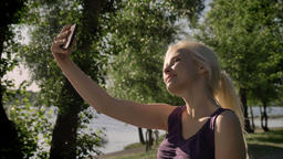 Young pretty blonde woman taking selfie with her phone, showing tongue and Footage