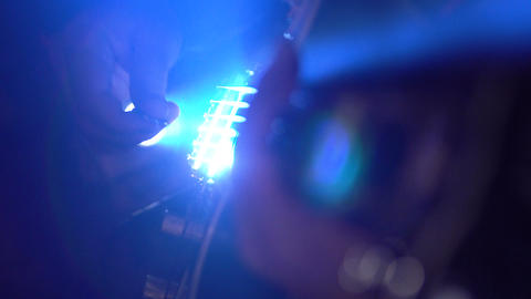 A man plays an electric guitar. Bright light through my hand. Slow motion Footage