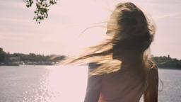 Young charming woman waving, touching her long hair and turning away, river Footage