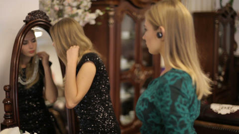 Two beautiful girls choose jewelry in front of a mirror in a chic room GIF