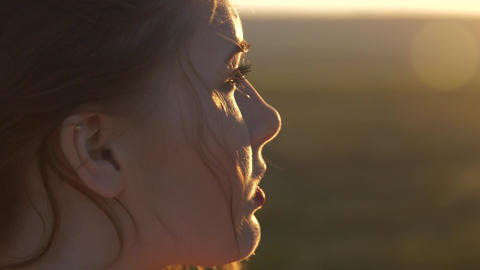 The face of a young beautiful woman who looks at the setting sun The wind shakes GIF