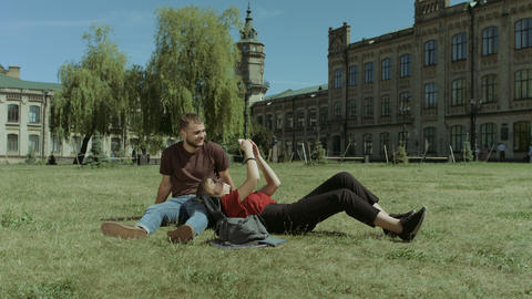 Couple of students using cellphone on campus lawn Footage