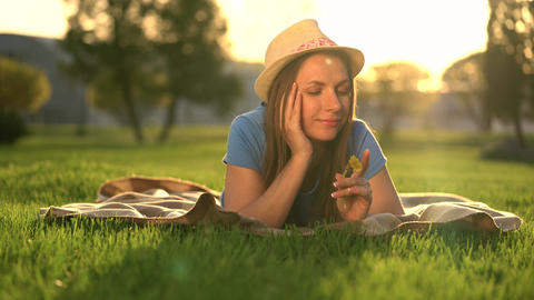 Girl with a dandelion in her hands relaxes lying down on a blanket in the park Footage
