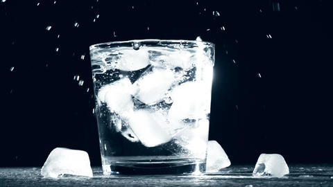 Splash of ice cube in glass water isolated on black background. Slow motion Footage
