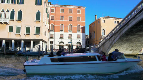 Motorboat with tourists sailing on canal in Venice, view on bridge and buildings Footage