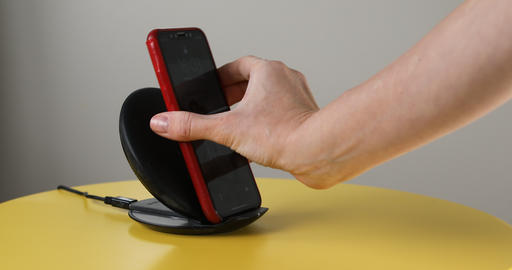 Hand smartphone is placed wireless fast charger Footage
