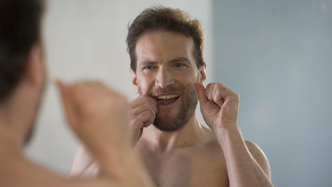 Guy taking care of oral hygiene, brushing his teeth with dental floss every day Live Action