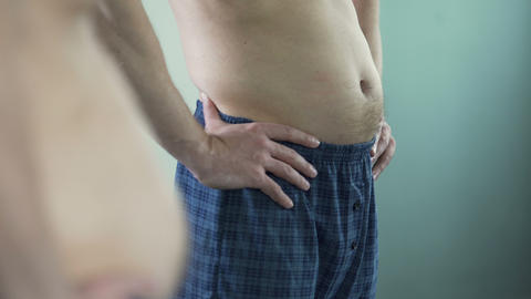 Middle-aged man looking in mirror at his tummy appeared during midlife crisis Footage