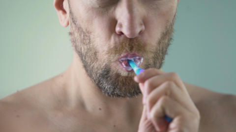 Bearded middle-aged man carefully brushing his teeth looking in mirror, close-up Footage