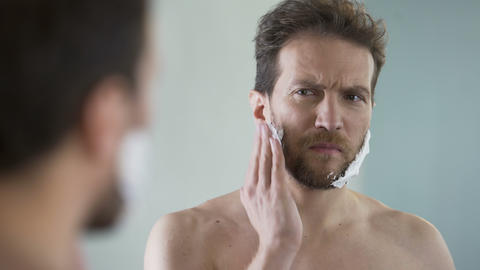 Middle-aged bearded man applying shaving foam on face, morning ritual, mirror Footage