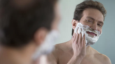 Happy and confident male putting shaving cream on his face before shaving Footage