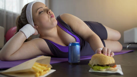 Happy self-confident obese girl eating greasy burger instead of sports workout Live Action