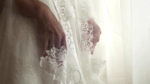 Hands of a bride who keep them hidden behind white dress with lace 21c Footage