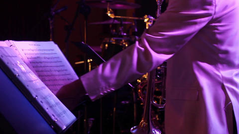 Man plays the trumpet during a performance his musical score sits in front of hi Footage