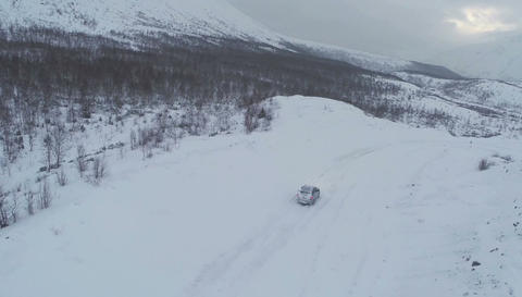 Aerial view of car driving on snowy mountain road Footage
