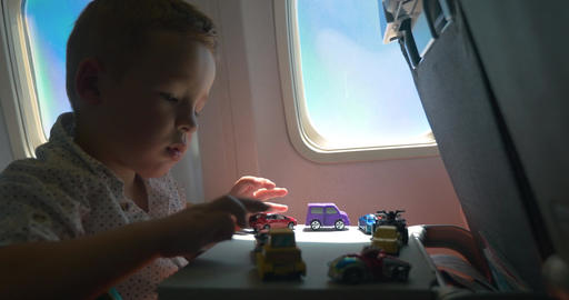 Little kid playing with toy cars in the airplane Footage