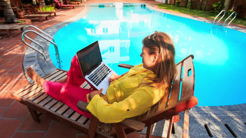 Blond Girl Sits on Folding Chair Works on Laptop by Pool Footage