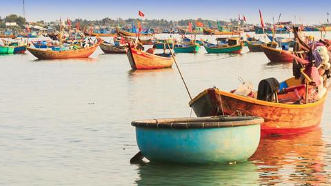Man Walks Throws Thing in Round Fishing Boat in Vietnam Footage