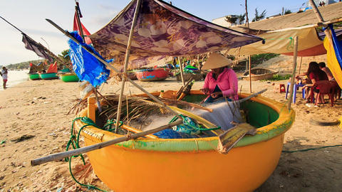 Woman Sits in Round Boat Mends Fishing Nets on Beach in Vietnam Footage