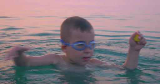 Little boy in goggles turning around himself Footage