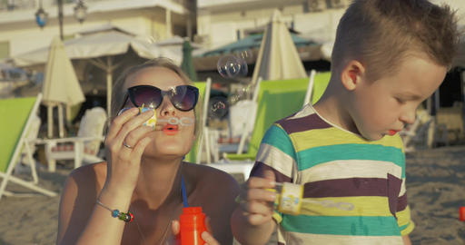 Mother and child blowing bubbles on the beach Footage