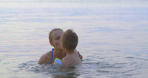 Mother with son bathing in sea and having fun Footage